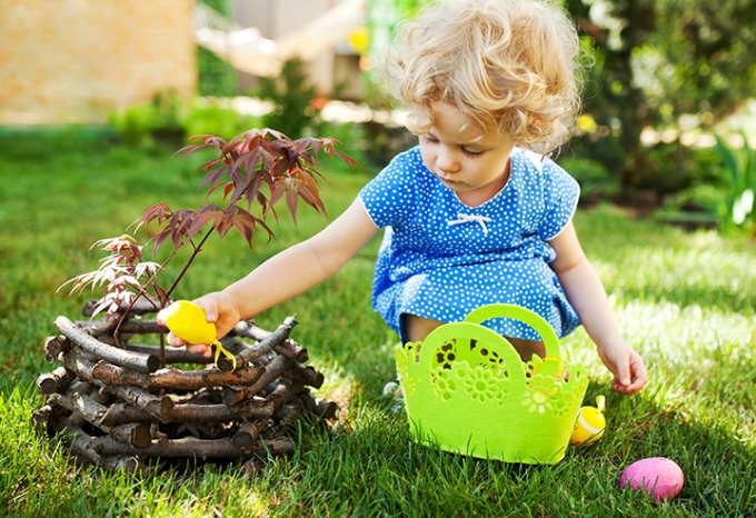 Little Girl on an Easter Egg hunt on a meadow in spring